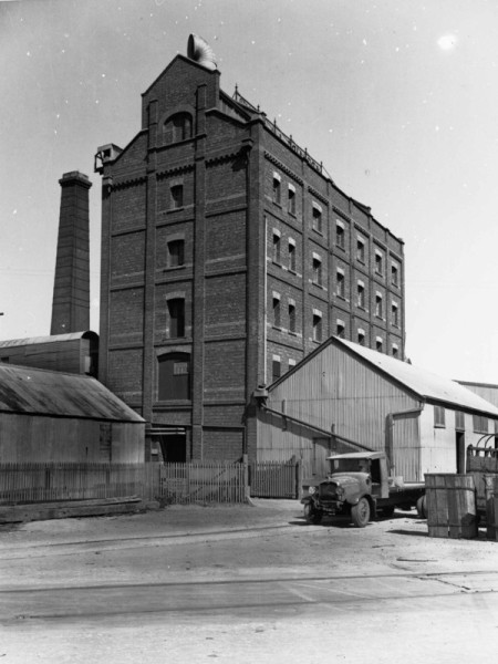 Image: Tall stone building surrounded by corrugated iron sheds and free standing stone chimney