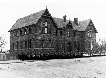 Image: large stone building with group of children in front